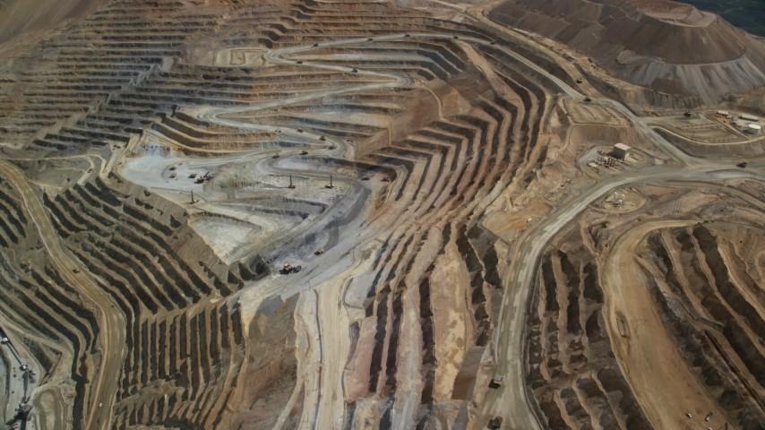 Flying away from gravel haulers, Bingham Canyon Mine, Utah Aerial Stock Footage | AX130_056