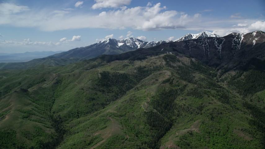 6K stock footage aerial video of approaching green ridges, snowy peaks, Oquirrh Mountains, Utah Aerial Stock Footage   AX130_058