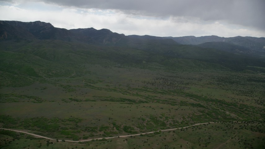 6K stock footage aerial video of approaching green hills, heavy clouds above, Wasatch Range, Utah Aerial Stock Footage | AX130_125