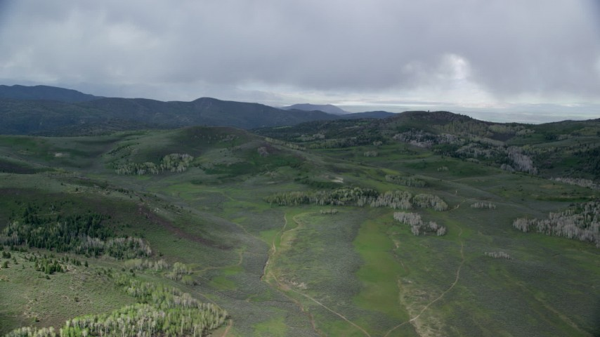6K stock footage aerial video of flying by green hills, trees, heavy clouds above, Wasatch Range, Utah Aerial Stock Footage | AX130_127