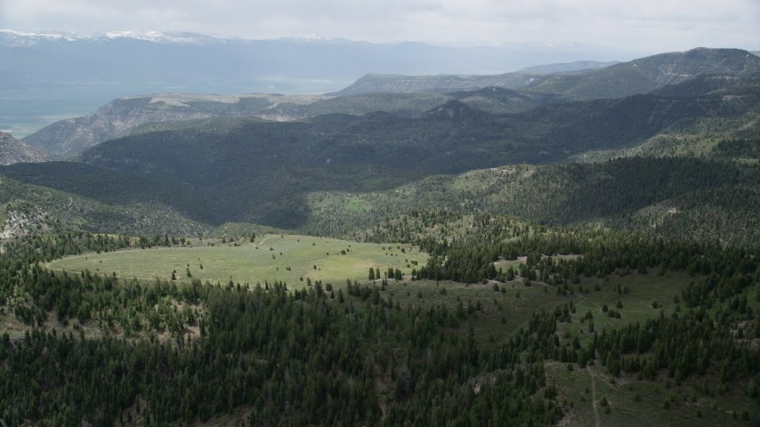 6K stock footage aerial video of flying over green mountains, trees, Wasatch Range, Utah Aerial Stock Footage | AX130_129