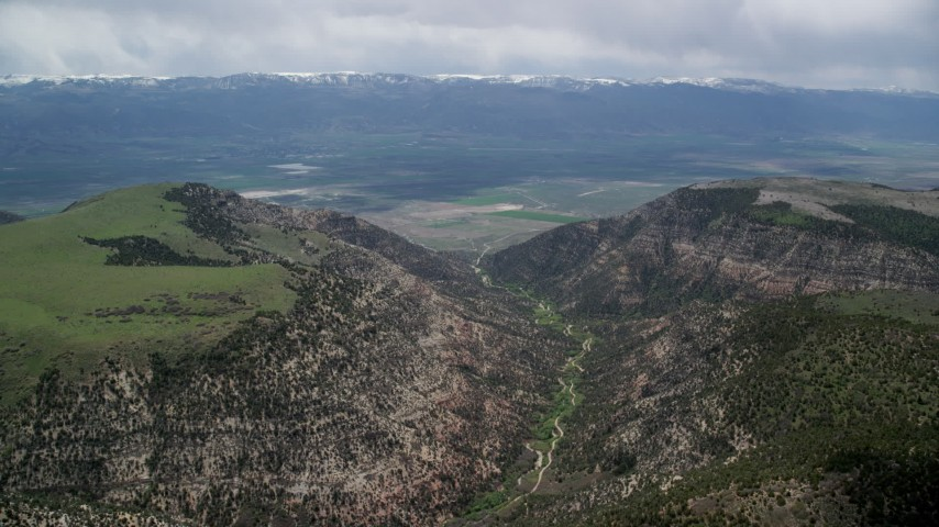 Approaching a valley over mountain peaks, Wasatch Range, Utah Aerial Stock Footage   AX130_133