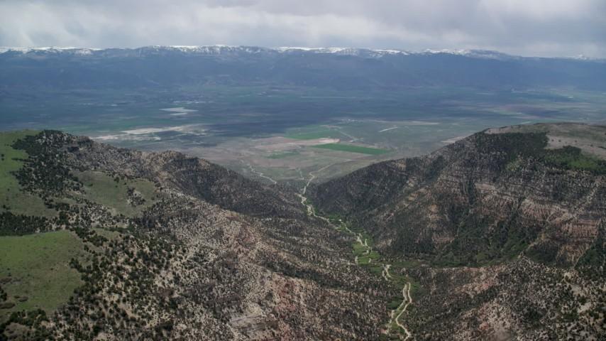6K stock footage aerial video of flying between mountain peaks, approaching valley, Wasatch Range, Utah Aerial Stock Footage | AX130_134