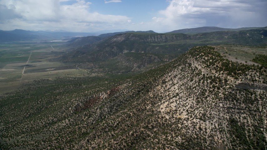 6K stock footage aerial video of flying by mountain peaks, slopes with trees, Wasatch Range, Utah Aerial Stock Footage | AX130_137