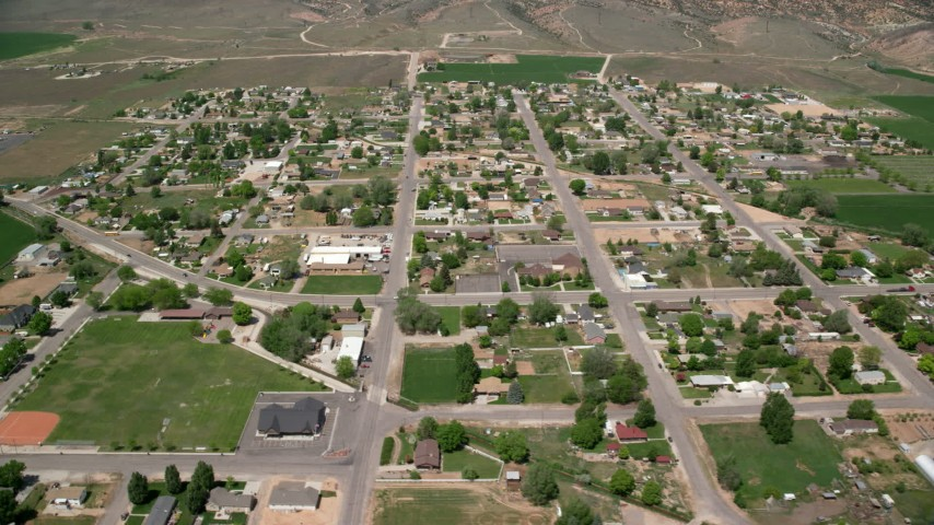 Flying by small rural town, surrounded by farmland, Aurora, Utah Aerial Stock Footage AX130_170