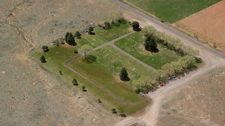 6K stock footage aerial video of orbiting a tiny cemetery by rural road, dirt fields, Bicknell, Utah Aerial Stock Footage | AX130_239