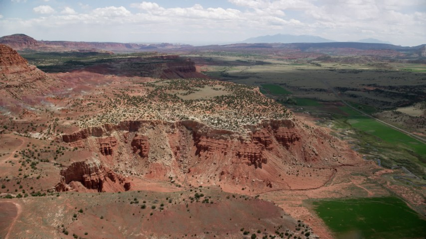 6K stock footage aerial video of approaching a mesa, surrounded by farmland, Capitol Reef National Park, Utah Aerial Stock Footage | AX130_241