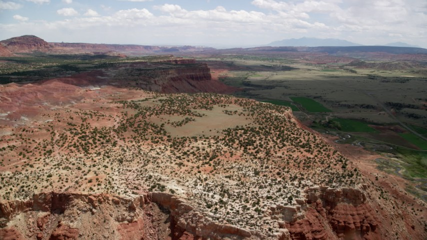 6K stock footage aerial video of flying over a mesa overlooking a green valley, farmland, Capitol Reef National Park, Utah Aerial Stock Footage | AX130_242