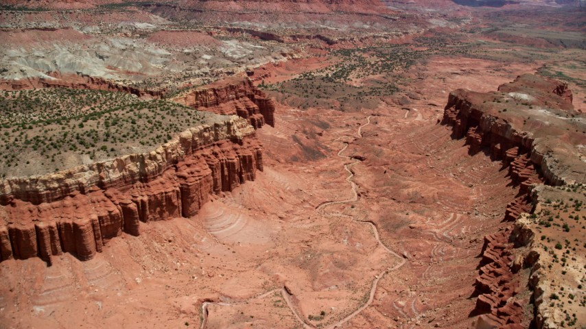 Fly over, tilt down to dry river bed in canyon between mesas, Capitol Reef National Park, Utah Aerial Stock Footage | AX130_250