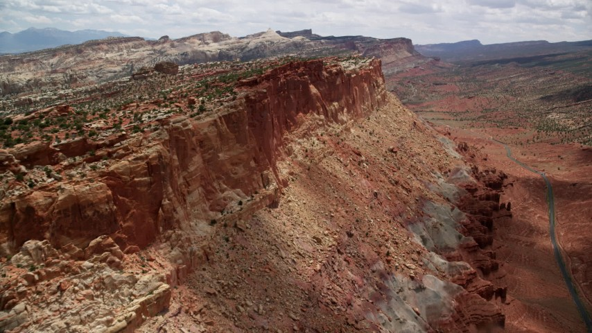 6K stock footage aerial video approach the side of a mesa, Waterpocket Fold rock formations in the distance, Capitol Reef National Park, Utah Aerial Stock Footage | AX130_269