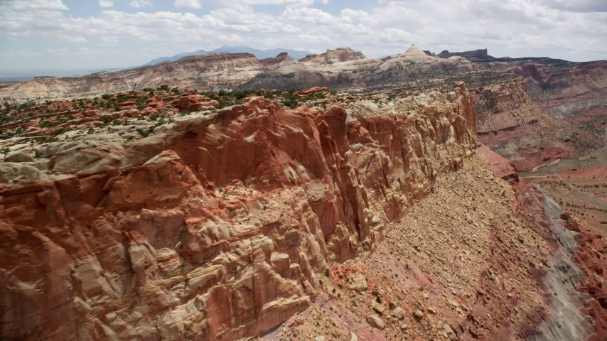 6K stock footage aerial video of mesa cliffs, Waterpocket Fold rock formations in the background, Capitol Reef National Park, Utah Aerial Stock Footage | AX130_271