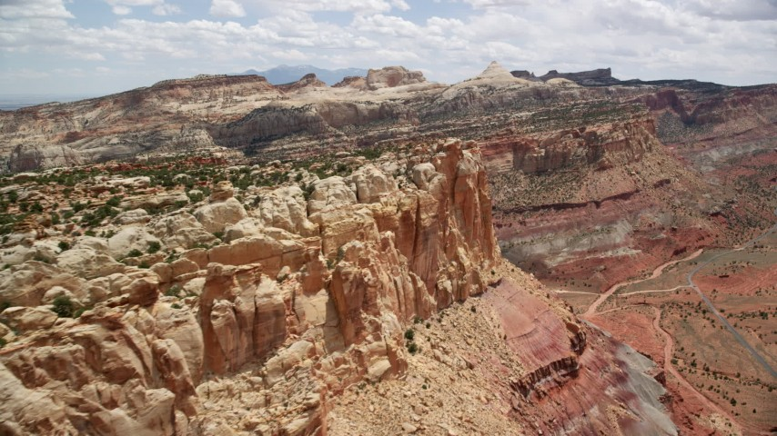6K stock footage aerial video of a rugged mesa cliff near Waterpocket Fold rock formations, Capitol Reef National Park, Utah Aerial Stock Footage | AX130_272