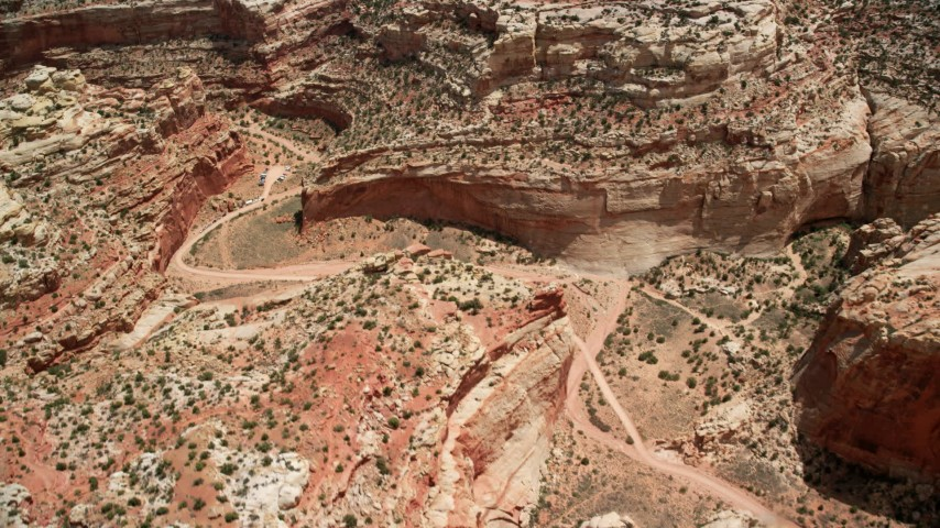 Bird's eye view flying over dirt road through a canyon, parked cars, Capitol Reef National Park, Utah Aerial Stock Footage | AX130_275