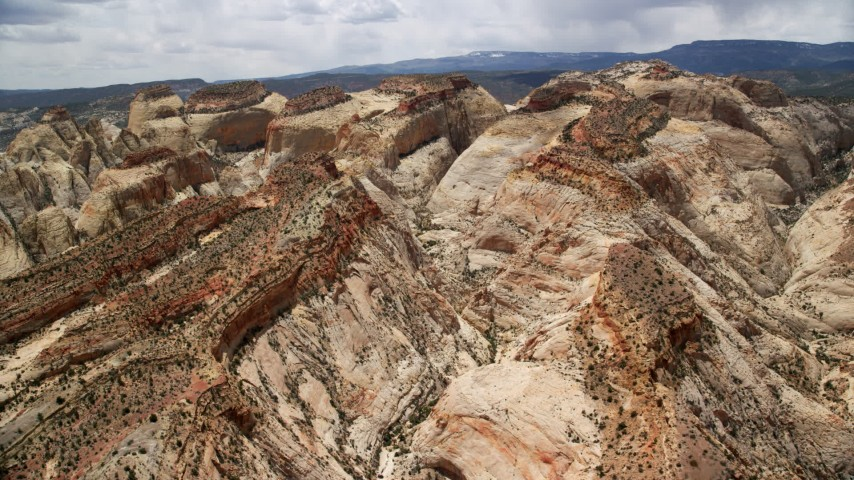 6K stock footage aerial video pan across and flyby canyons in Waterpocket Fold rock formations, Capitol Reef National Park, Utah Aerial Stock Footage | AX130_304