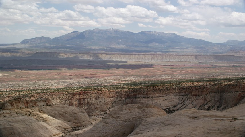 Flying by distant mesas, mountains, Capitol Reef National Park, Utah Aerial Stock Footage | AX130_318