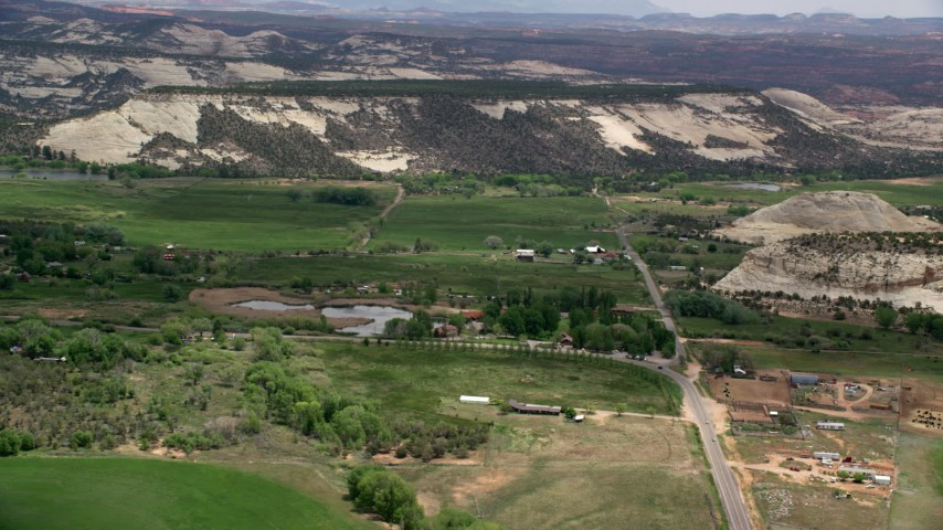 6K stock footage aerial video of passing a rural town near pond, green fields, flat mountain, Boulder, Utah Aerial Stock Footage | AX130_372
