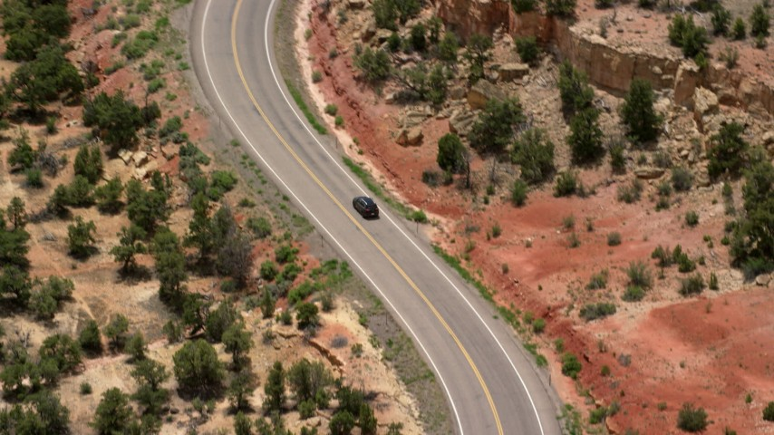 6K stock footage aerial video of tracking a black SUV, tilt up to Route 12 winding past trees, Boulder, Utah Aerial Stock Footage | AX130_379