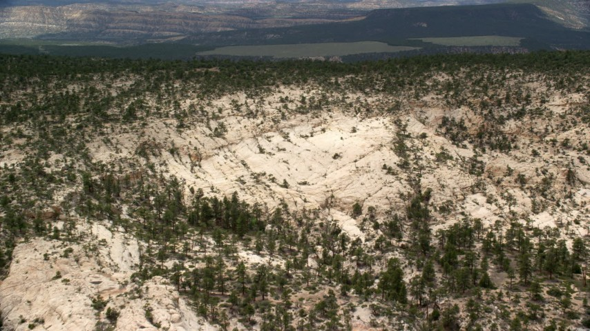 Flying over mountain ridge, approaching a distant plateau, Grand Staircase-Escalante National Monument, Utah Aerial Stock Footage | AX130_388