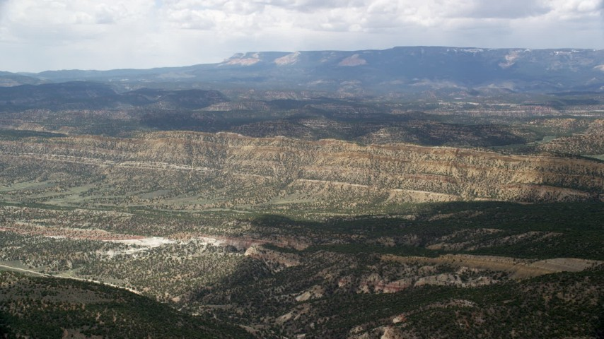 Flying over a valley, approaching a mountain ridge, Grand Staircase-Escalante National Monument, Utah Aerial Stock Footage | AX130_394