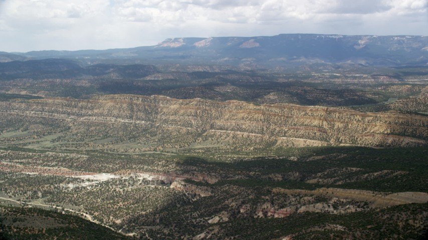 6K stock footage aerial video of flying over a valley, approaching a mountain ridge, Grand Staircase-Escalante National Monument, Utah Aerial Stock Footage | AX130_394