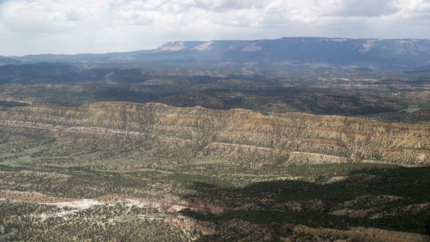 Flying over valley, approaching a mountain ridge, Grand Staircase-Escalante National Monument, Utah Aerial Stock Footage | AX130_395