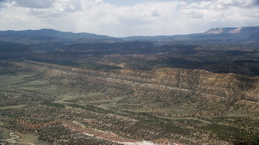 Approaching a mountain ridge from over a wide valley, Grand Staircase-Escalante National Monument, Utah Aerial Stock Footage | AX130_396