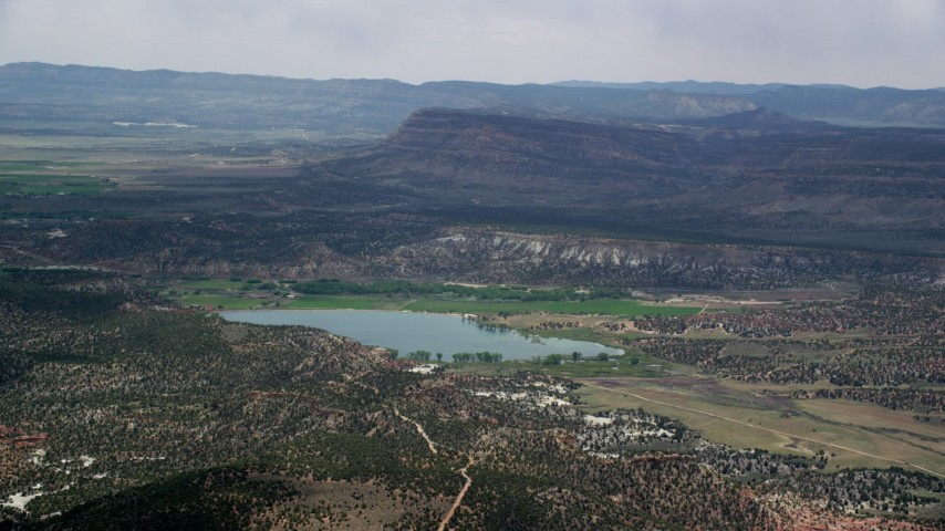 Flying by a wide hollow reservoir, Grand Staircase-Escalante National Monument, Utah Aerial Stock Footage | AX130_397