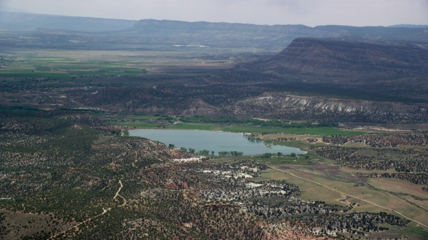 Flying by a wide hollow reservoir, Grand Staircase-Escalante National Monument, Utah Aerial Stock Footage | AX130_398