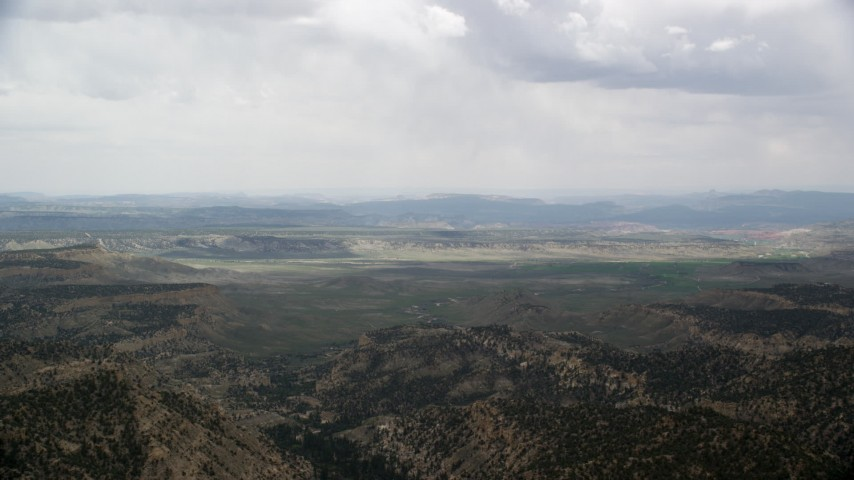 Flying by green valley beyond mountain ridges, Grand Staircase-Escalante National Monument, Utah Aerial Stock Footage | AX130_419