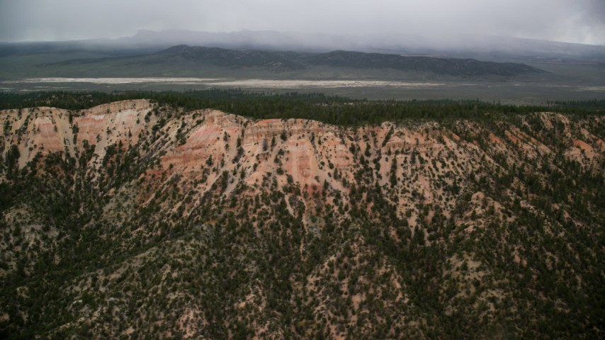 Flying by mountain ridge, trees, dry lake in the distance, Bryce Canyon National Park, Utah Aerial Stock Footage | AX130_420