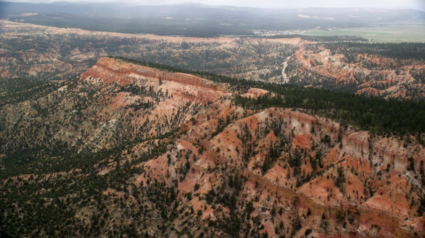 6K stock footage aerial video of flying by long mesa with trees, desert vegetation, Bryce Canyon National Park, Utah Aerial Stock Footage | AX130_424