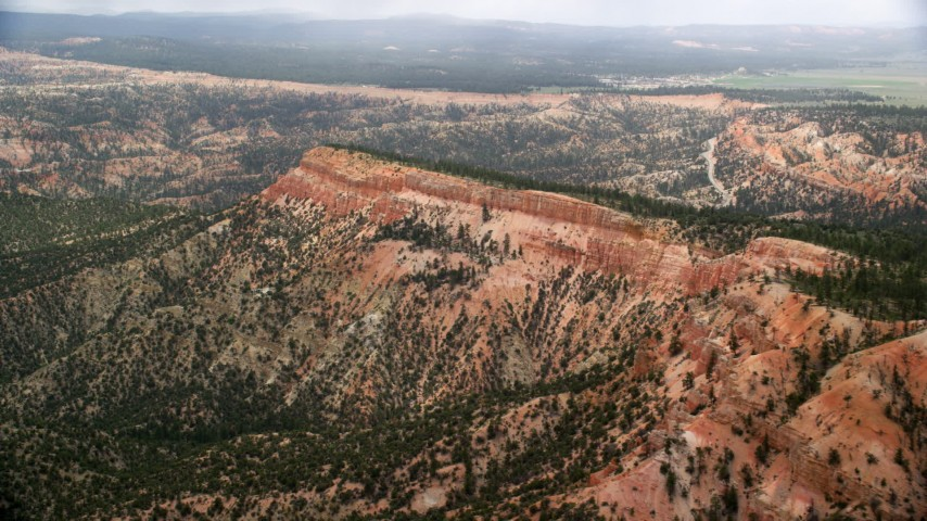 Flying by a log mesa, steep cliffs, trees and desert vegetation, Bryce Canyon National Park, Utah Aerial Stock Footage | AX130_425