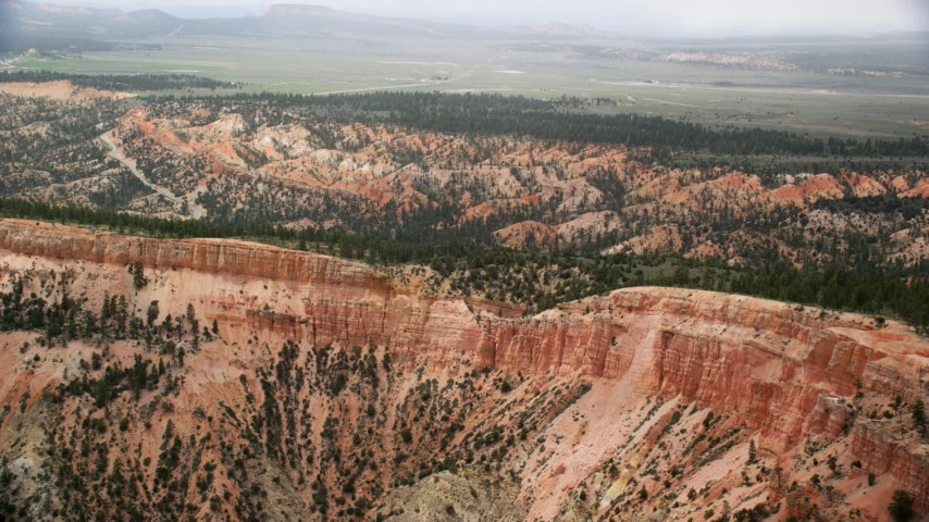 Flying by steep mesa slopes, trees, desert vegetation; Bryce Canyon National Park, Utah Aerial Stock Footage | AX130_426