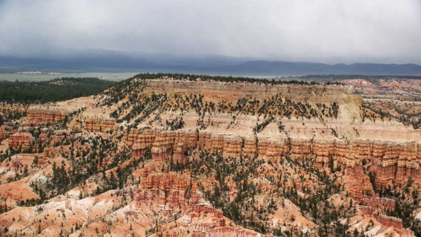 6K stock footage aerial video of passing by groups of hoodoos around base of mesa, Bryce Canyon National Park, Utah Aerial Stock Footage | AX130_431