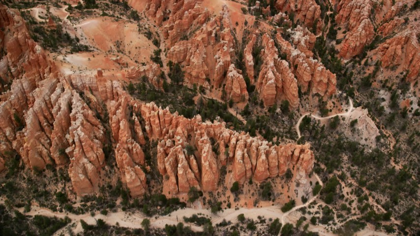 Bird's eye view flying over hoodoos, buttes, dirt roads, Bryce Canyon National Park, Utah Aerial Stock Footage AX130_433