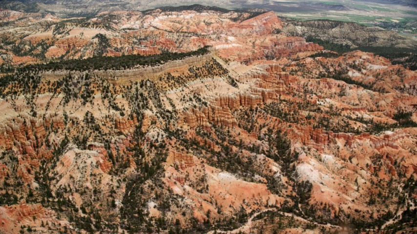 Flying by hills around a mesa, groups of hoodoos, Bryce Canyon National Park, Utah Aerial Stock Footage | AX130_440