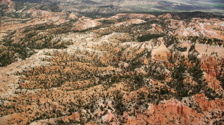 Flying by buttes, hills, small groups of hoodoos, Bryce Canyon National Park, Utah Aerial Stock Footage | AX130_443