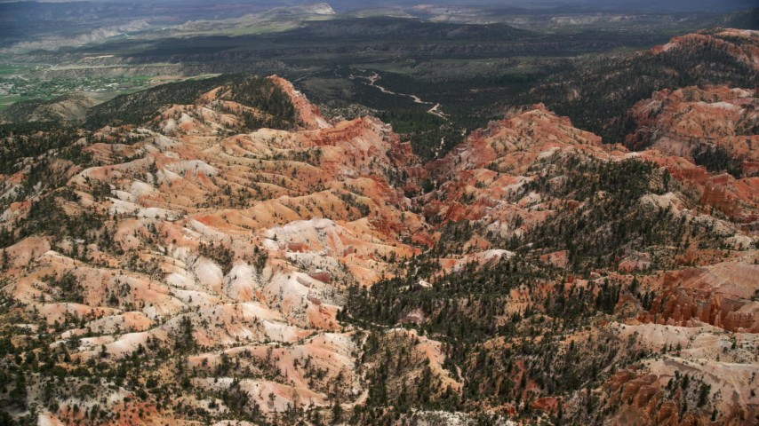 Orbiting hills, trees, dirt road winding through canyon, Bryce Canyon National Park, Utah Aerial Stock Footage | AX130_446