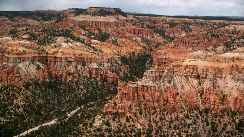 Flying by hoodoos, buttes, canyon, mesa in the background, Bryce Canyon National Park, Utah Aerial Stock Footage AX130_450