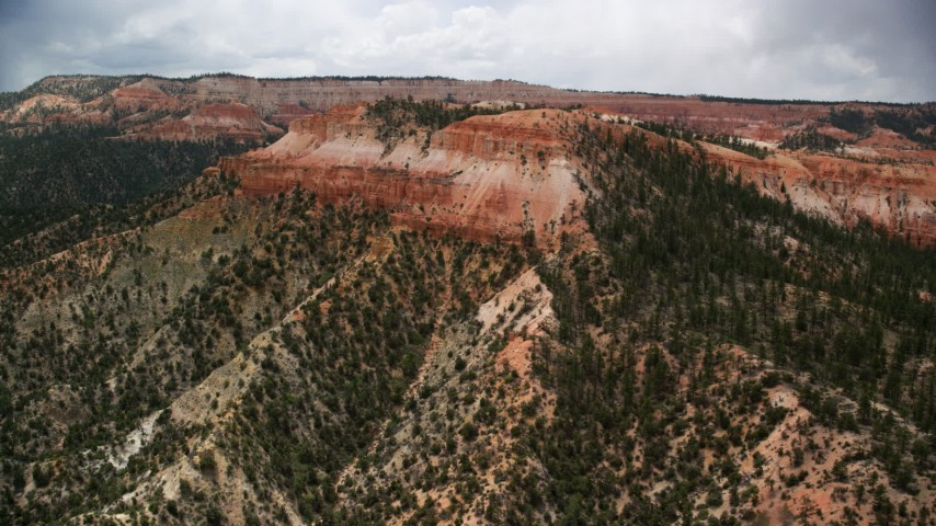 Flying by small mesa with hoodoos, trees, desert vegetation, Bryce Canyon National Park, Utah Aerial Stock Footage | AX130_451