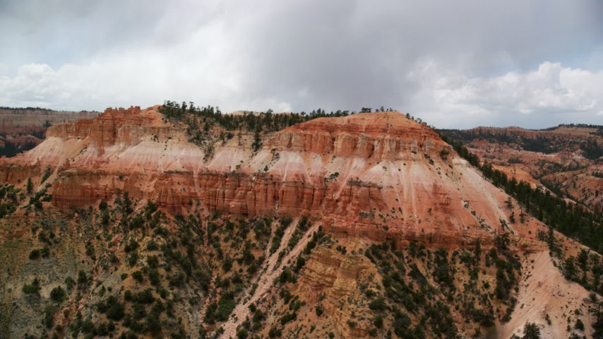 Flying by small mesa with hoodoos, trees, desert vegetation, Bryce Canyon National Park, Utah Aerial Stock Footage | AX130_452