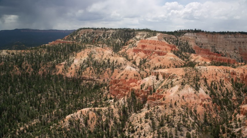Flying by groups of hoodoos and a large mesa, Bryce Canyon National Park, Utah Aerial Stock Footage | AX130_456