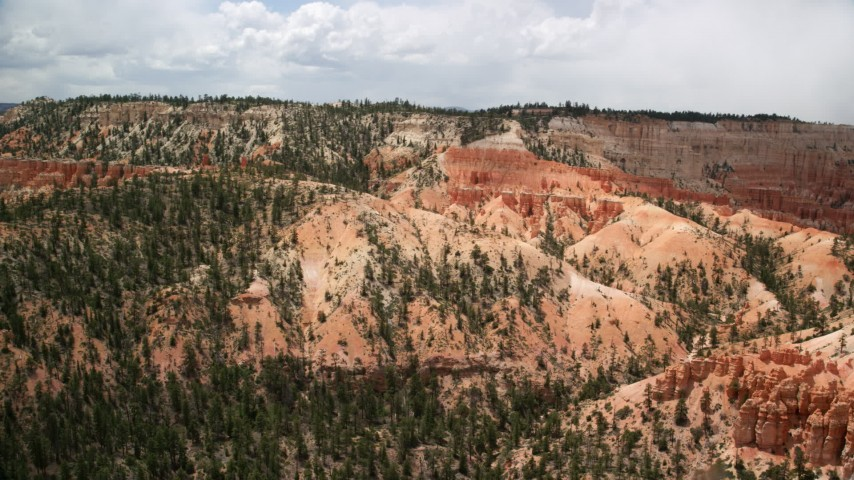 6K stock footage aerial video of groups of hoodoos near a large mesa, Bryce Canyon National Park, Utah Aerial Stock Footage | AX130_457