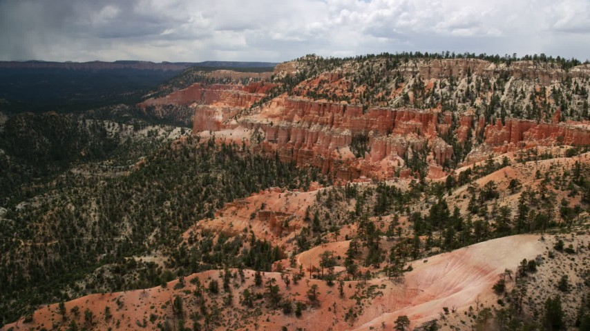 Flying by hoodoos on a mesa slope, Bryce Canyon National Park, Utah Aerial Stock Footage | AX130_458