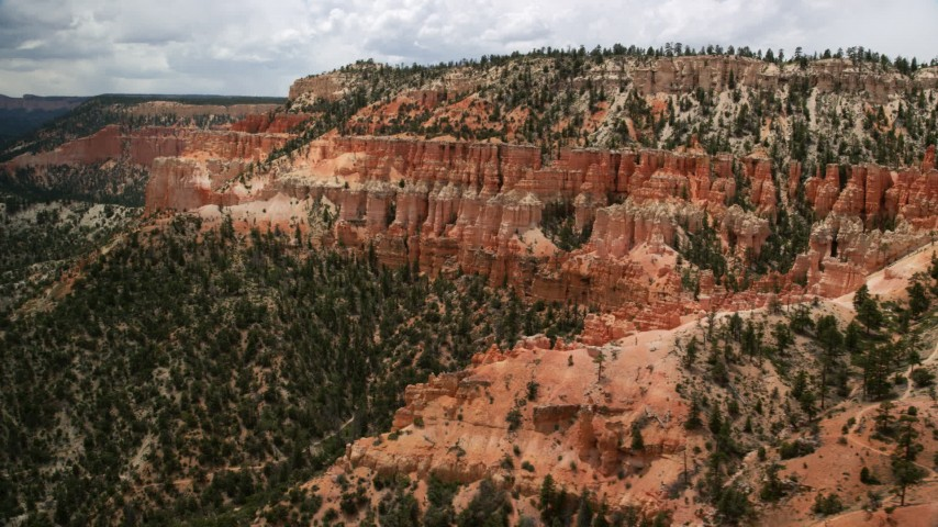 6K stock footage aerial video of passing by hoodoos on the slope of a mesa, Bryce Canyon National Park, Utah Aerial Stock Footage | AX130_459