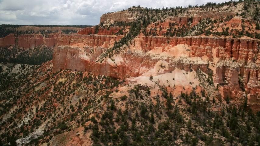 6K stock footage aerial video pan across hoodoos, steep mesa slope, revealing more mesas, Bryce Canyon National Park, Utah Aerial Stock Footage | AX130_460