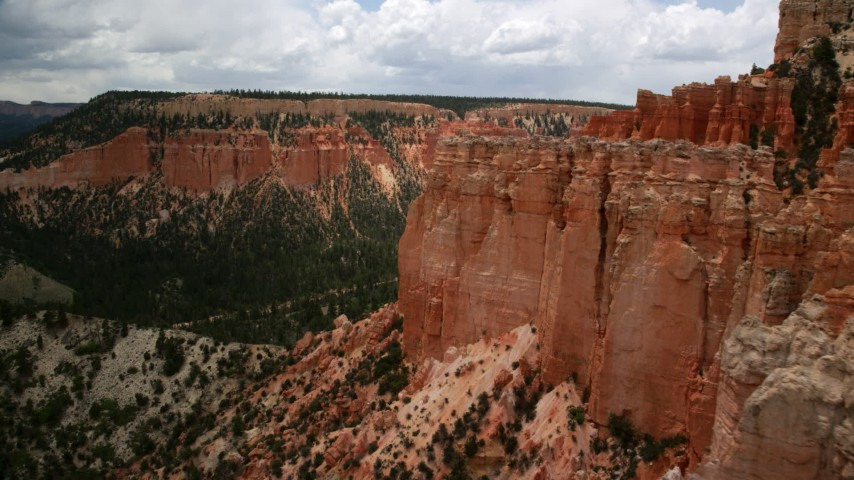 6K stock footage aerial video of flying by hoodoos on a steep mesa cliff and across a canyon, Bryce Canyon National Park, Utah Aerial Stock Footage | AX130_462