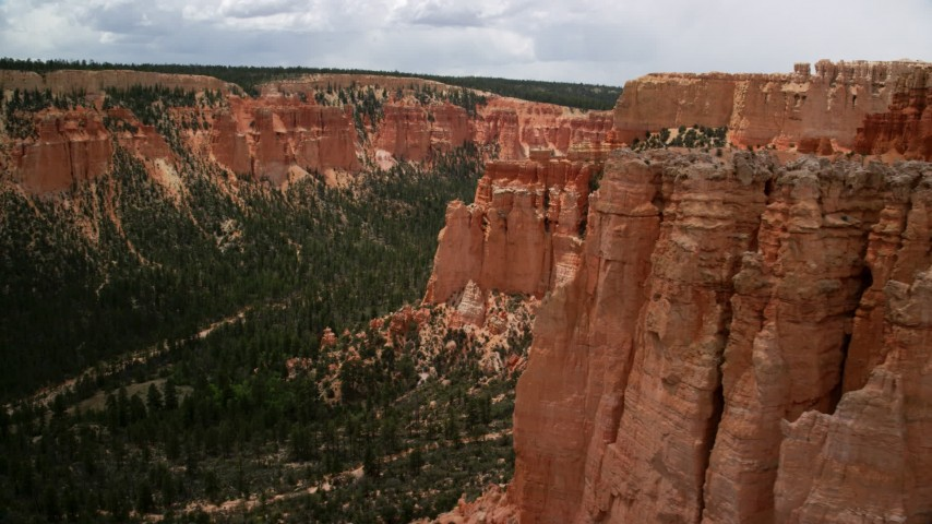 Flying by hoodoos on mesa cliffs, tree-covered canyon, Bryce Canyon National Park, Utah Aerial Stock Footage AX130_463