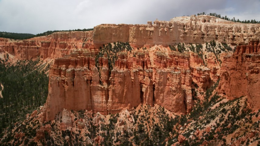 Flying by hoodoos on side of a mesa, revealing tree-covered slopes, Bryce Canyon National Park, Utah Aerial Stock Footage AX130_464