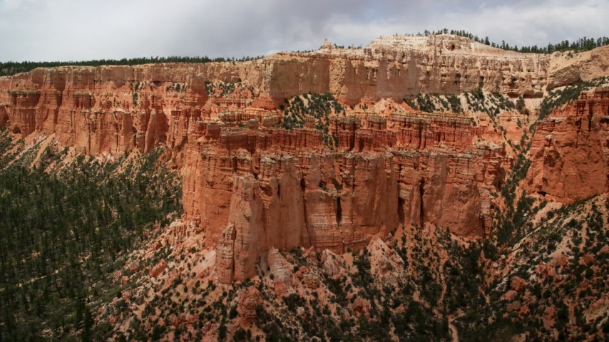 6K stock footage aerial video of flying away from hoodoos, mesa cliff, tree-covered slopes, Bryce Canyon National Park, Utah Aerial Stock Footage   AX130_465